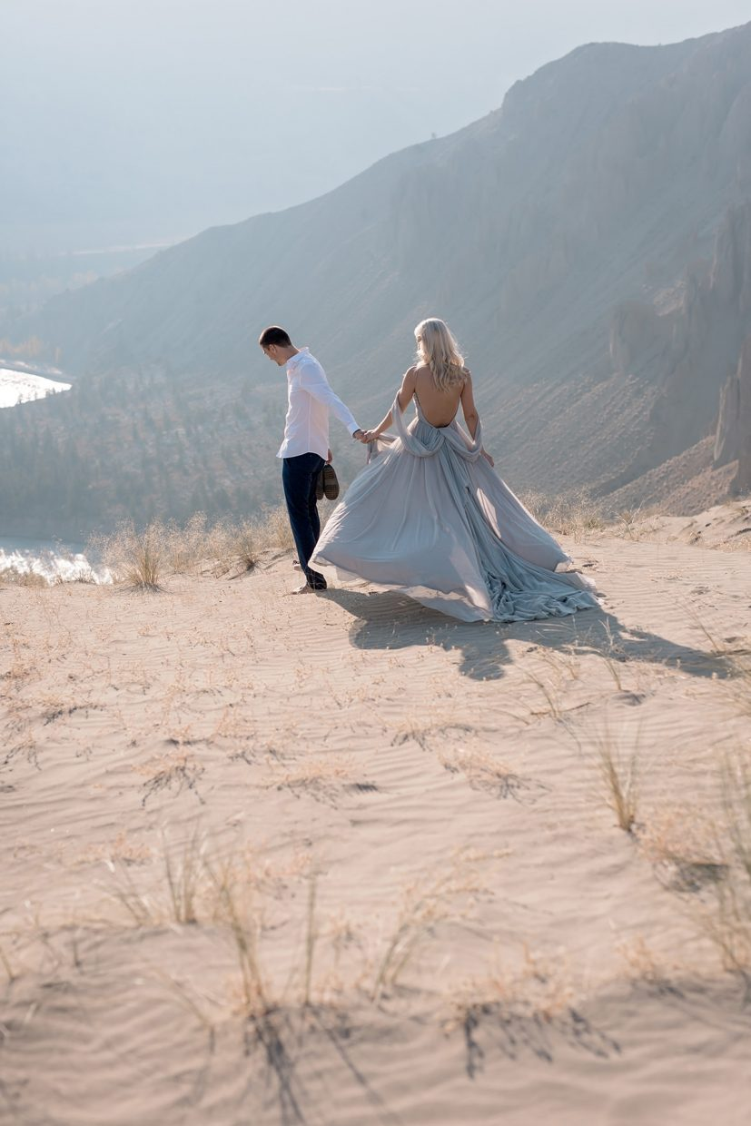 engaged couple in sand dunes, bride wearing a blue dress