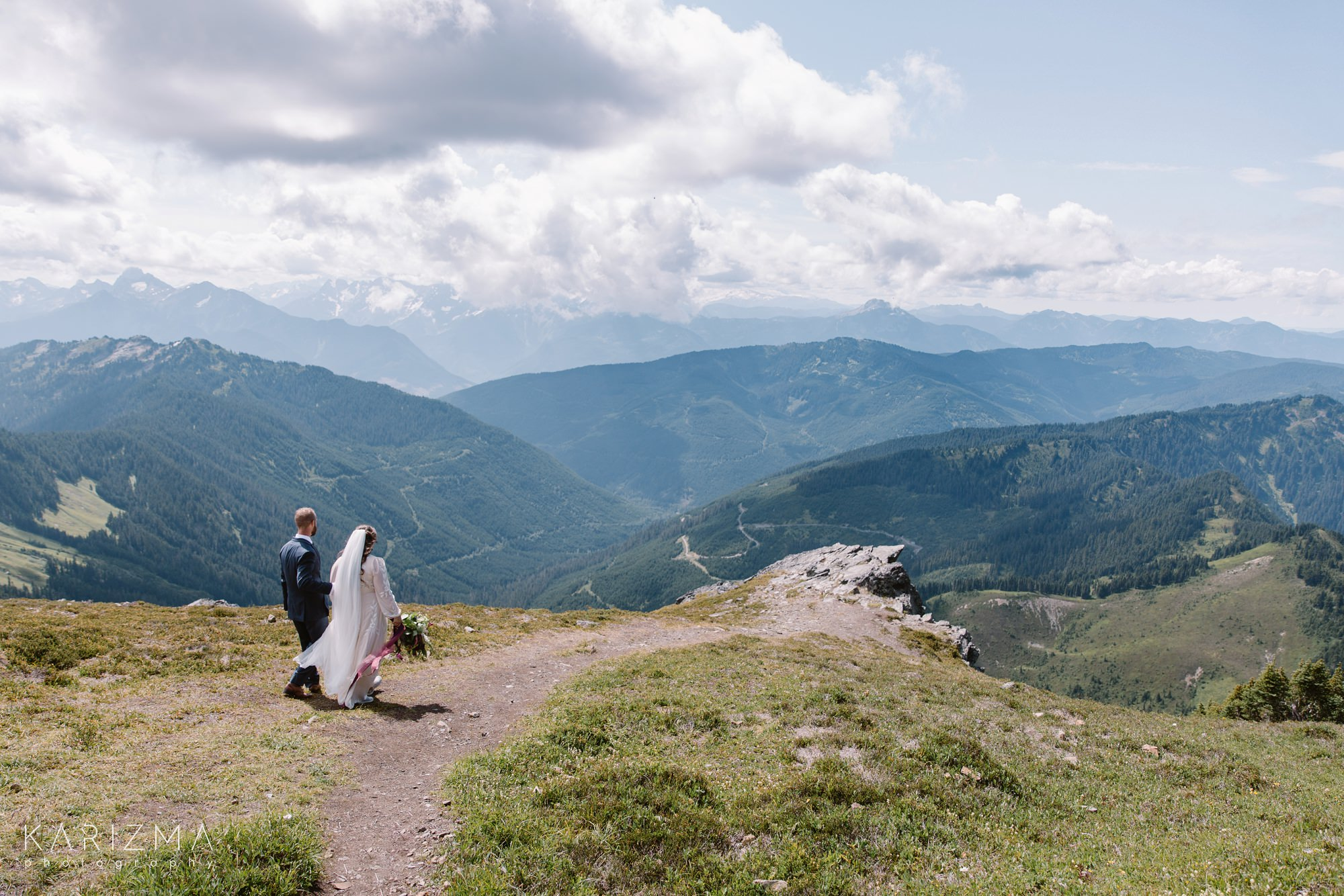 Bride and groom are walking to the location of their mountain elopement ceremony