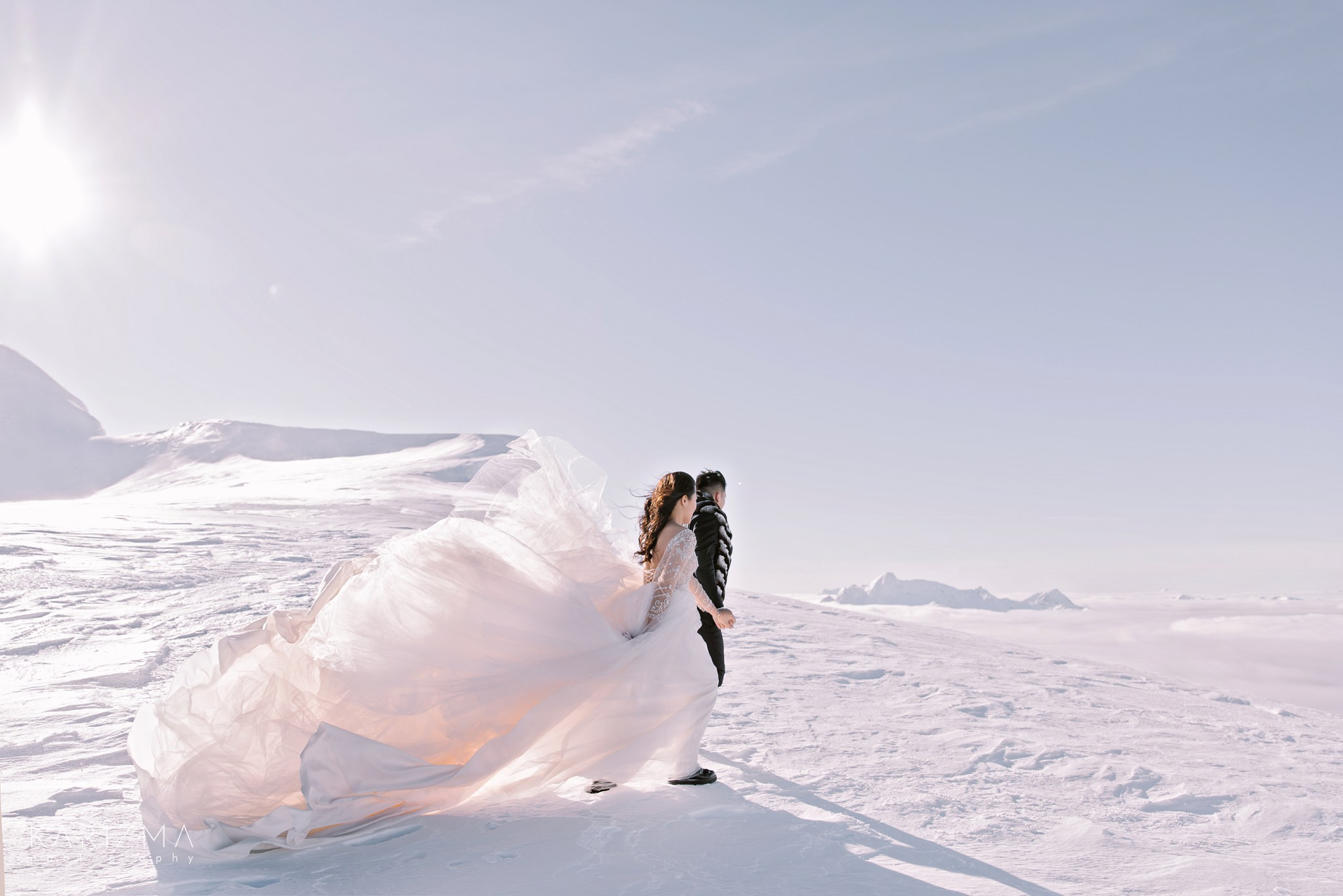 Bride and groom walking on the snow in the mountains