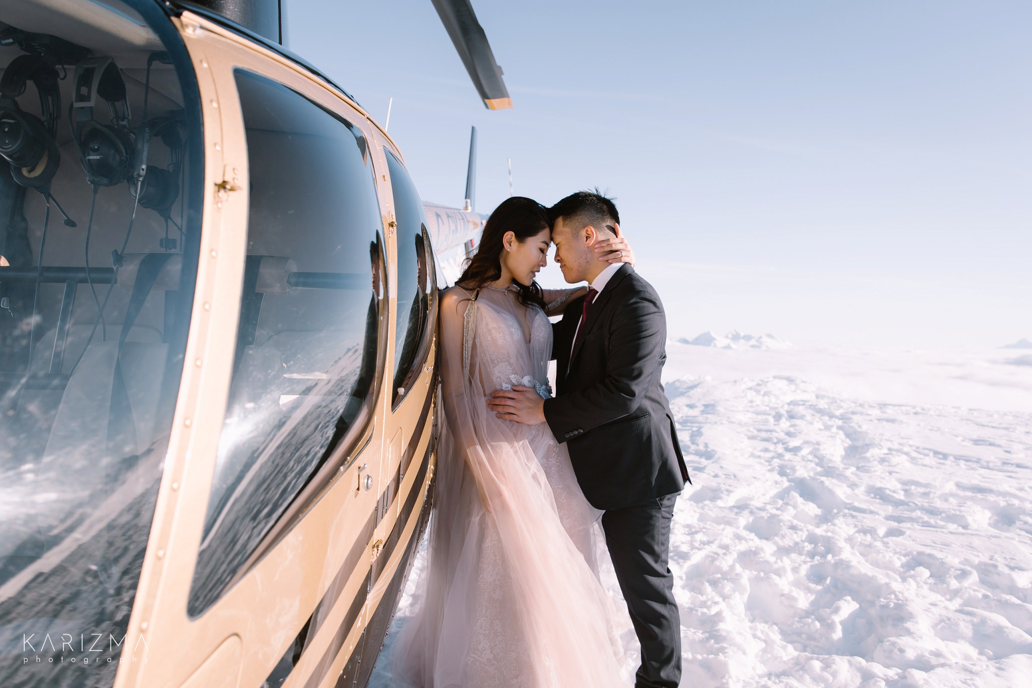 Bride and groom near the helicopter on the top of the mountain in Whistler