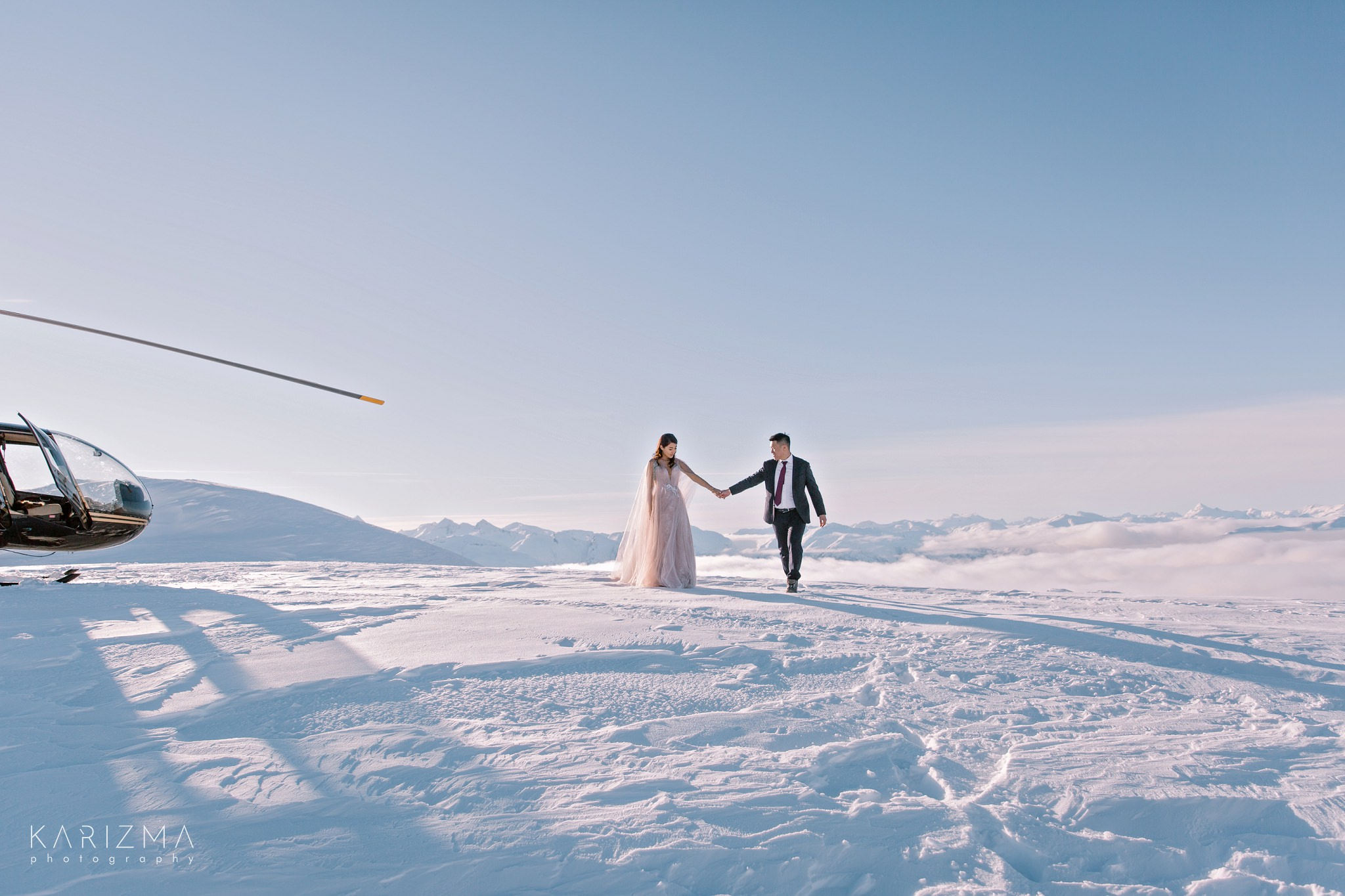 Bride and groom walking hand in hand near the helicopter in the mountains of British Columbia