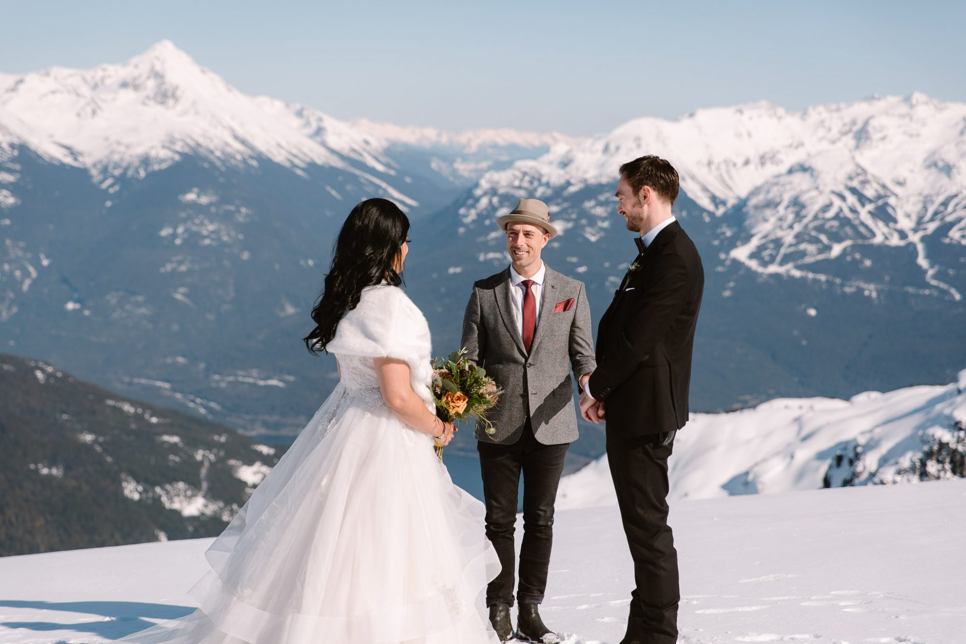 helicopter elopement in Whistler - wedding ceremony with bride and groom and a pastor with mountain backdrop
