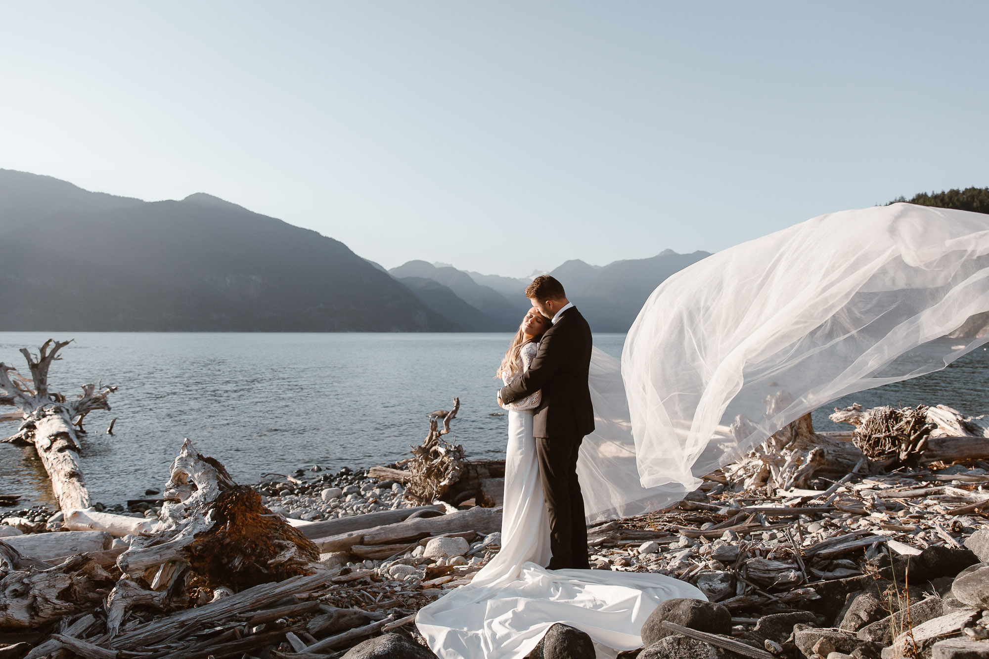 Bride and groom posing at the beach with stunting mountains view for their wedding photos