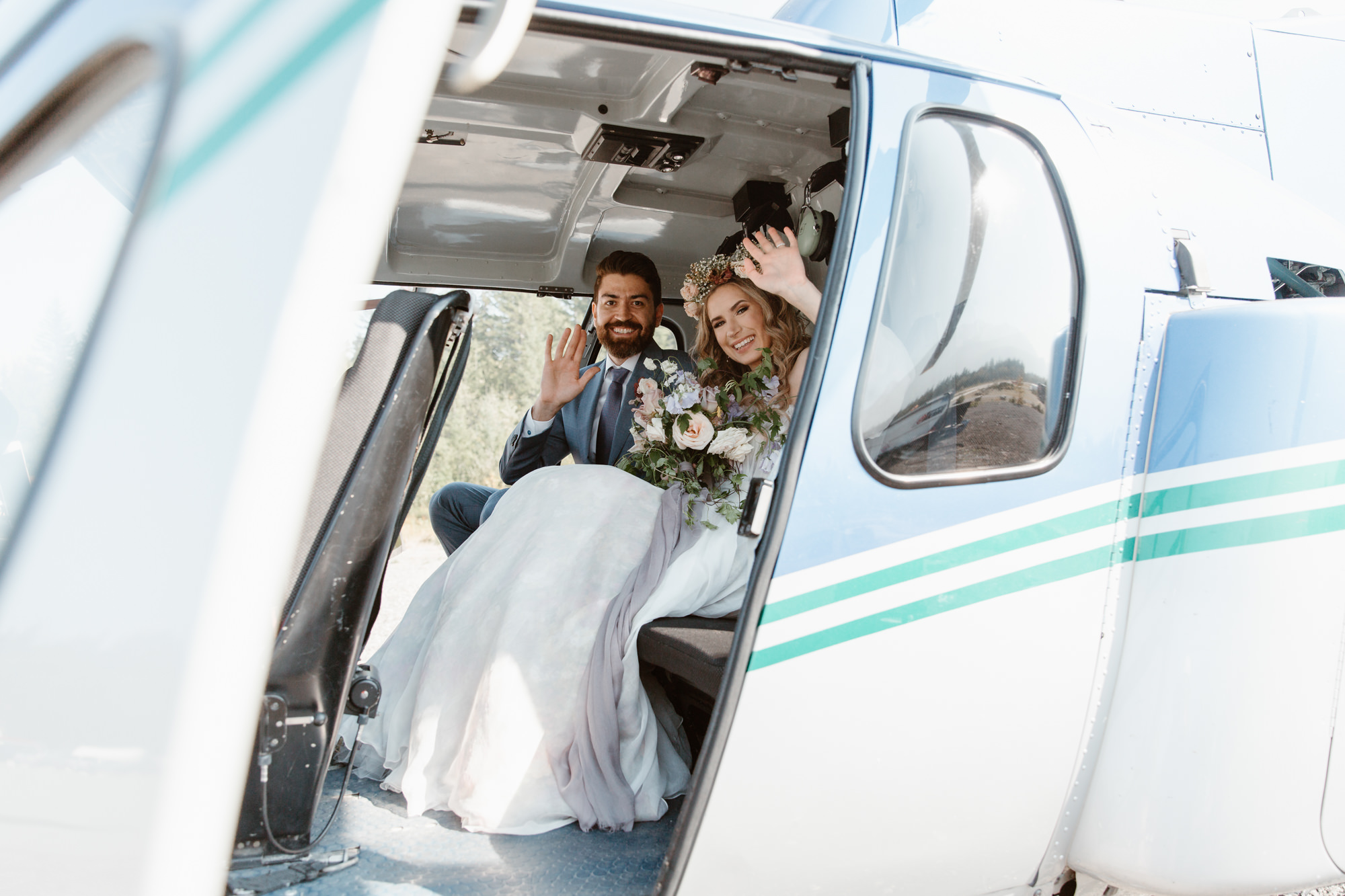 Bride and groom in the helicopter taking off for their photo session in the mountains