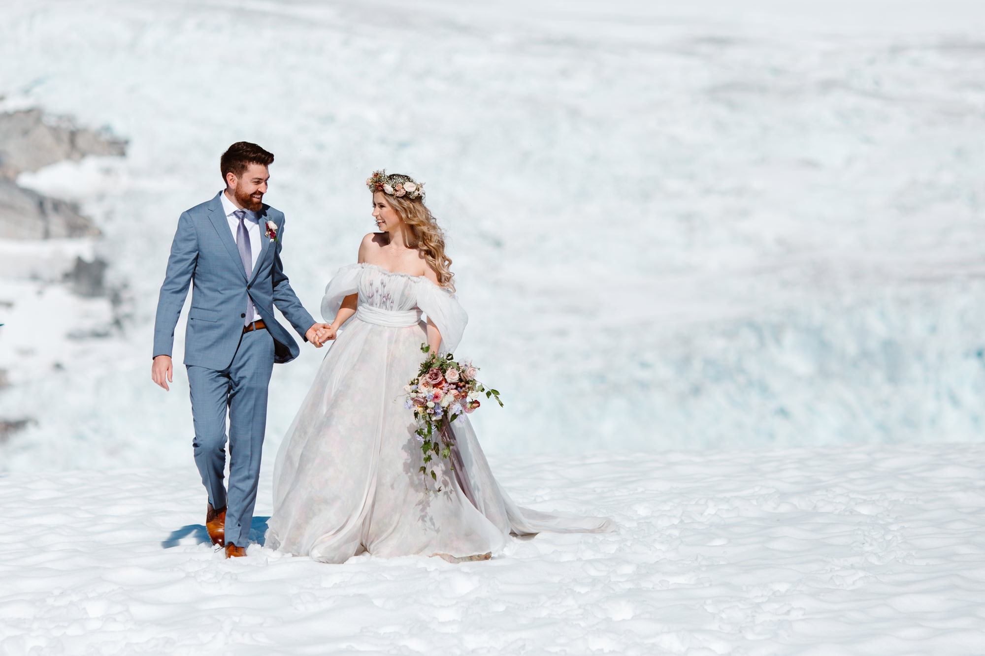 Happy bride and groom walking on the snow in the mountains during their whistler helicopter elopement