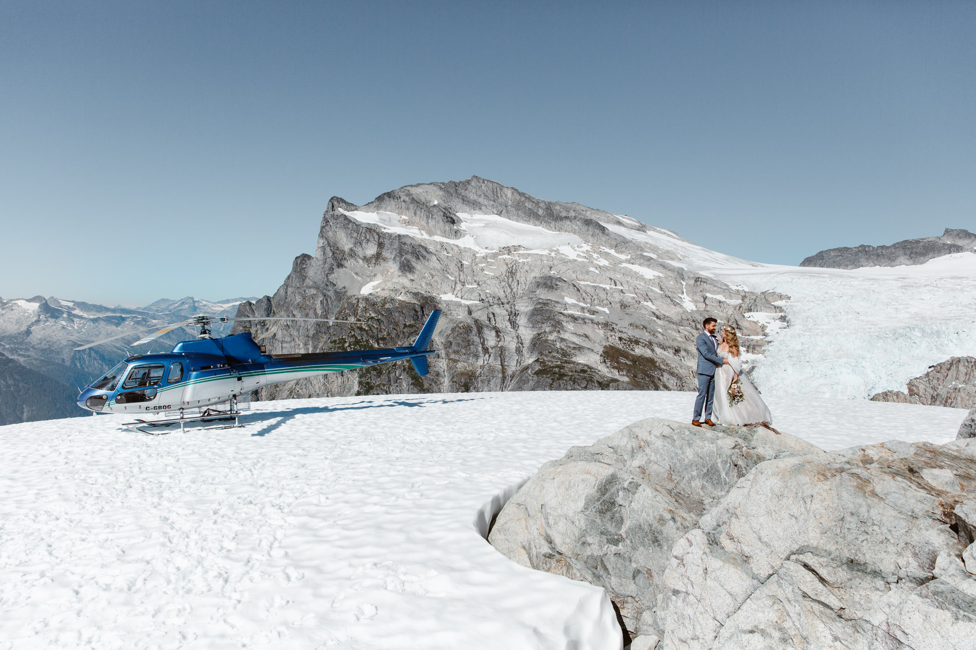Bride and groom posing for wedding photos in the mountains near the helicopter with the glacier on the background