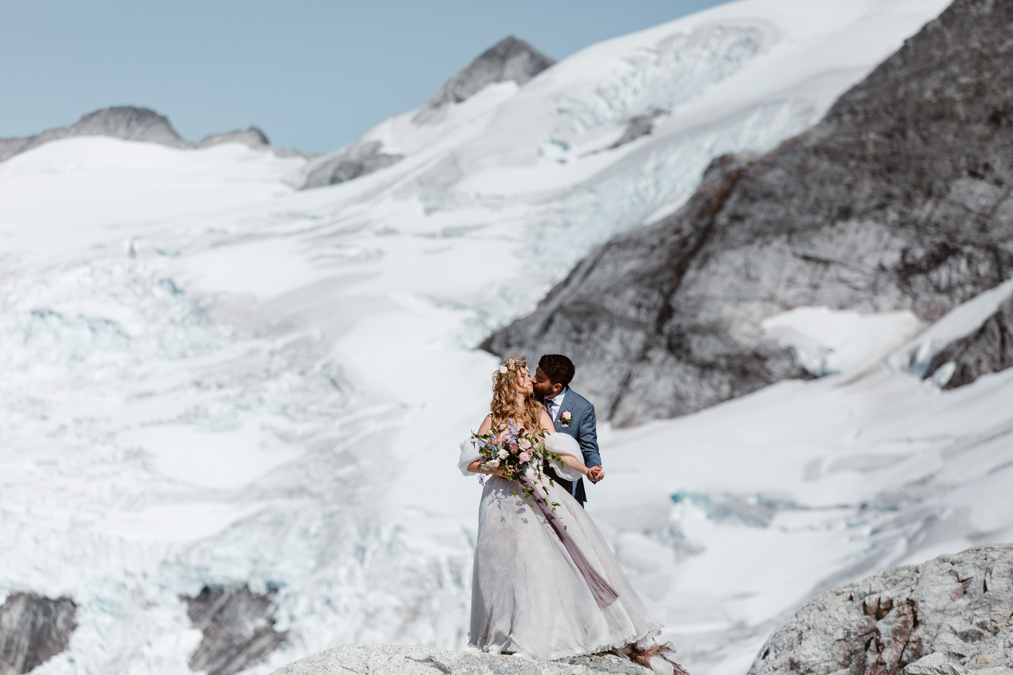Bride and groom standing on the cliff with a beautiful glacier on the background during their Whistler Helicopter Elopement