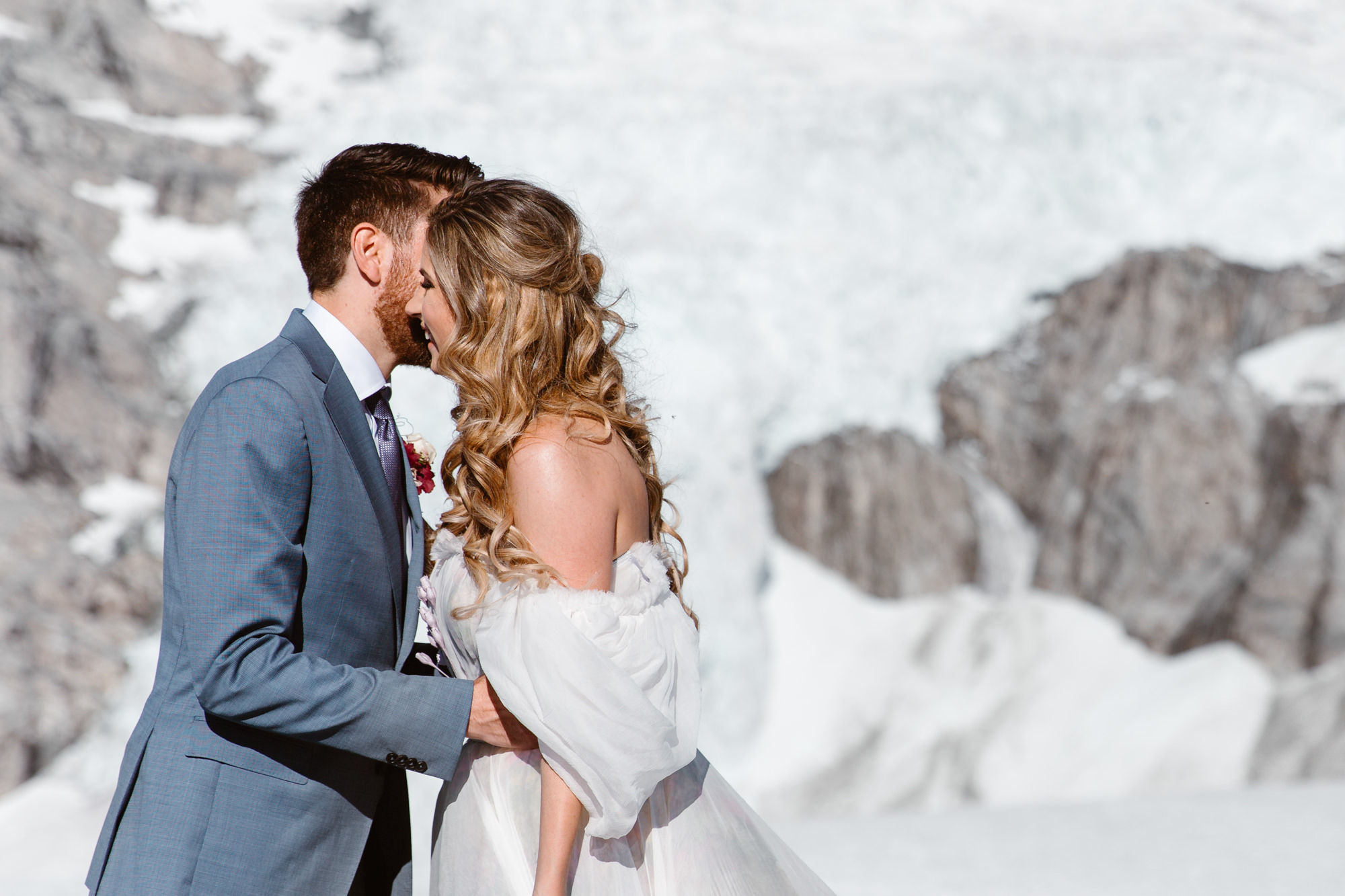 Groom is kissing the happy bride in the mountains during their Whistler Helicopter Elopement