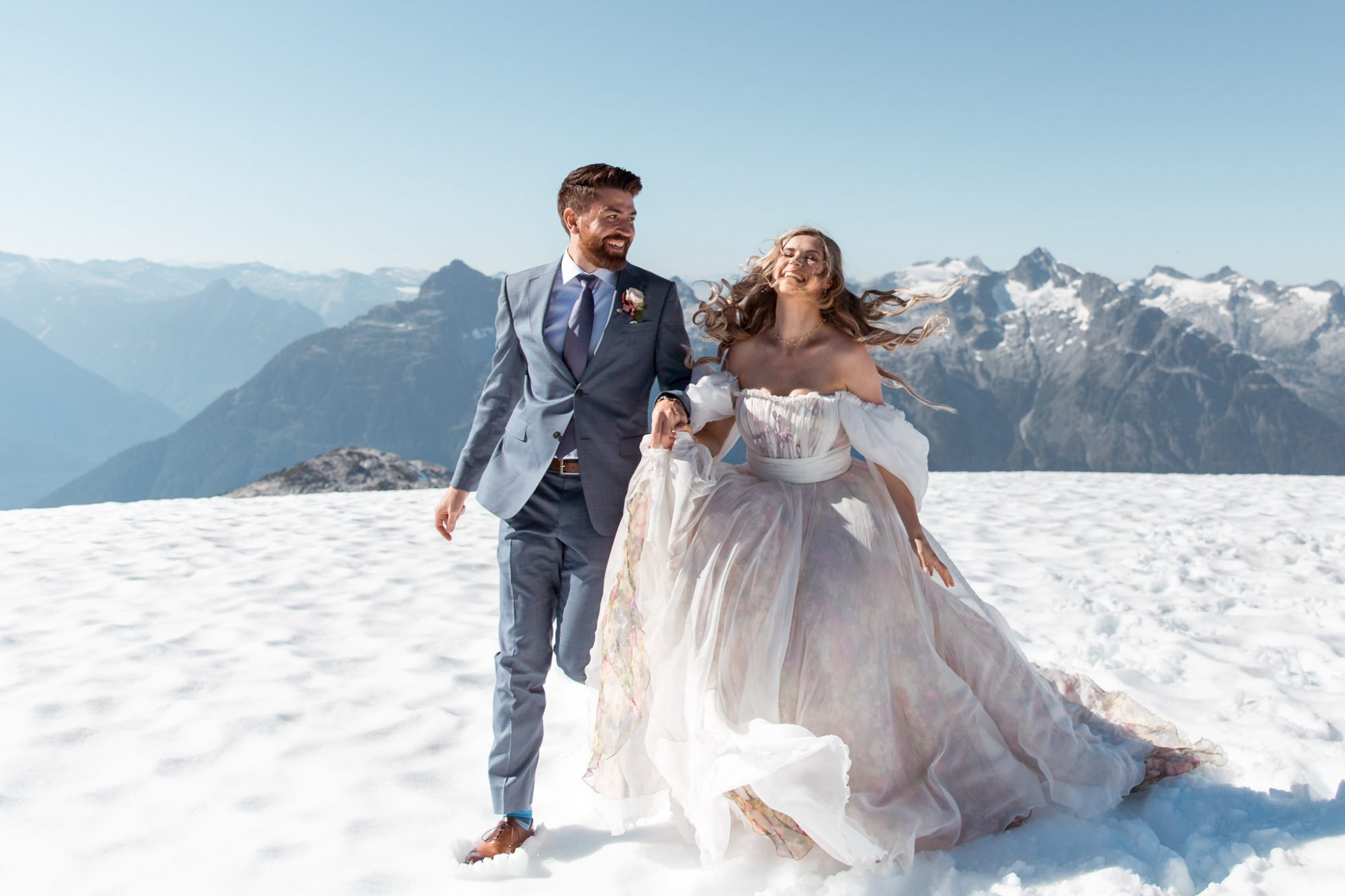 Happy smiling bride and groom running in the snow surrounded by the mountains during their whistler helicopter elopement