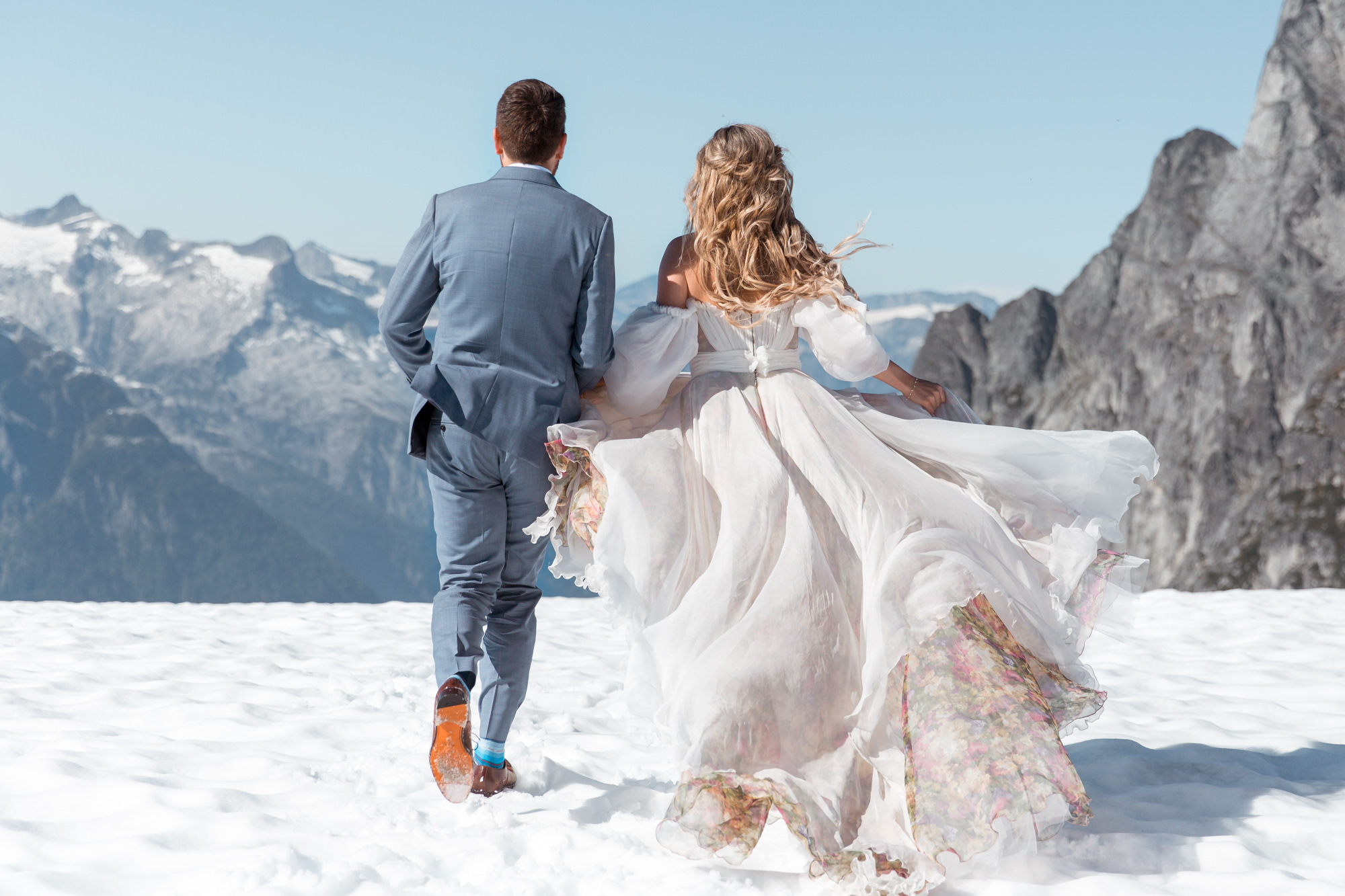 Bride and groom is running in the snow towards the mountains