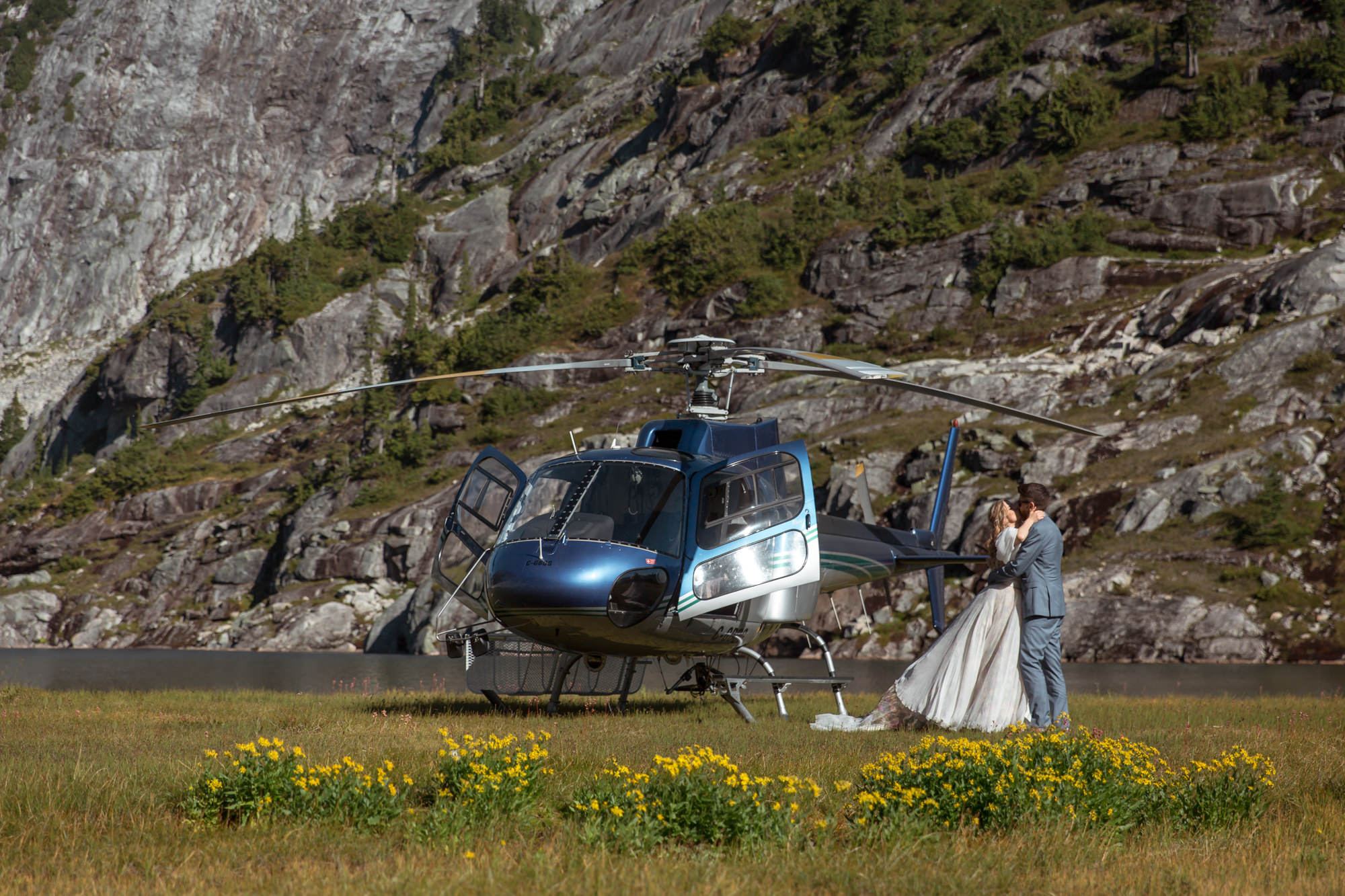 Couple kissing near helicopter by mountain lake in Whistler