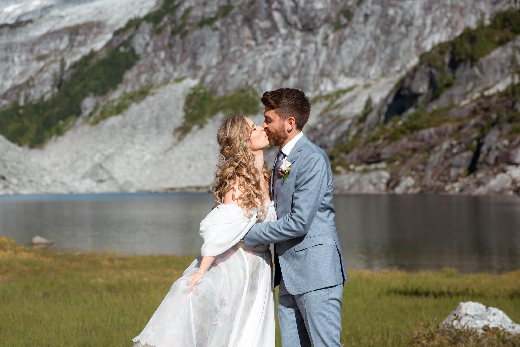 Couple kissing during their wedding photo session by the alpine lake