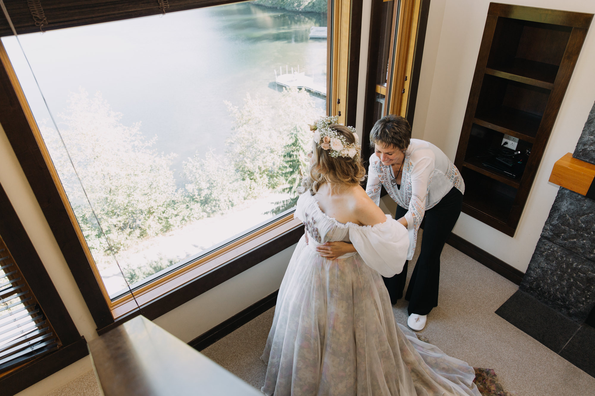 Bride putting her floral wedding dress Hilori by Rara Avis and her mother helping her