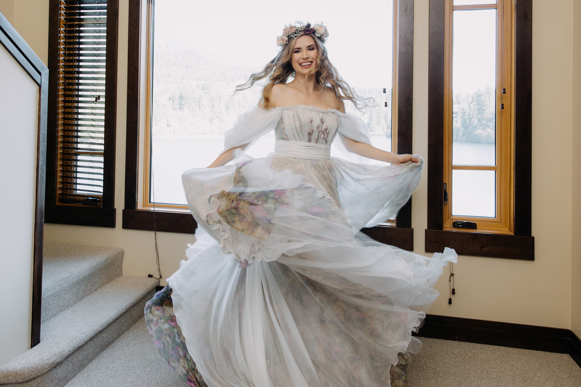 Happy bride twirling in her floral wedding dress before her intimate wedding ceremony in Whistler