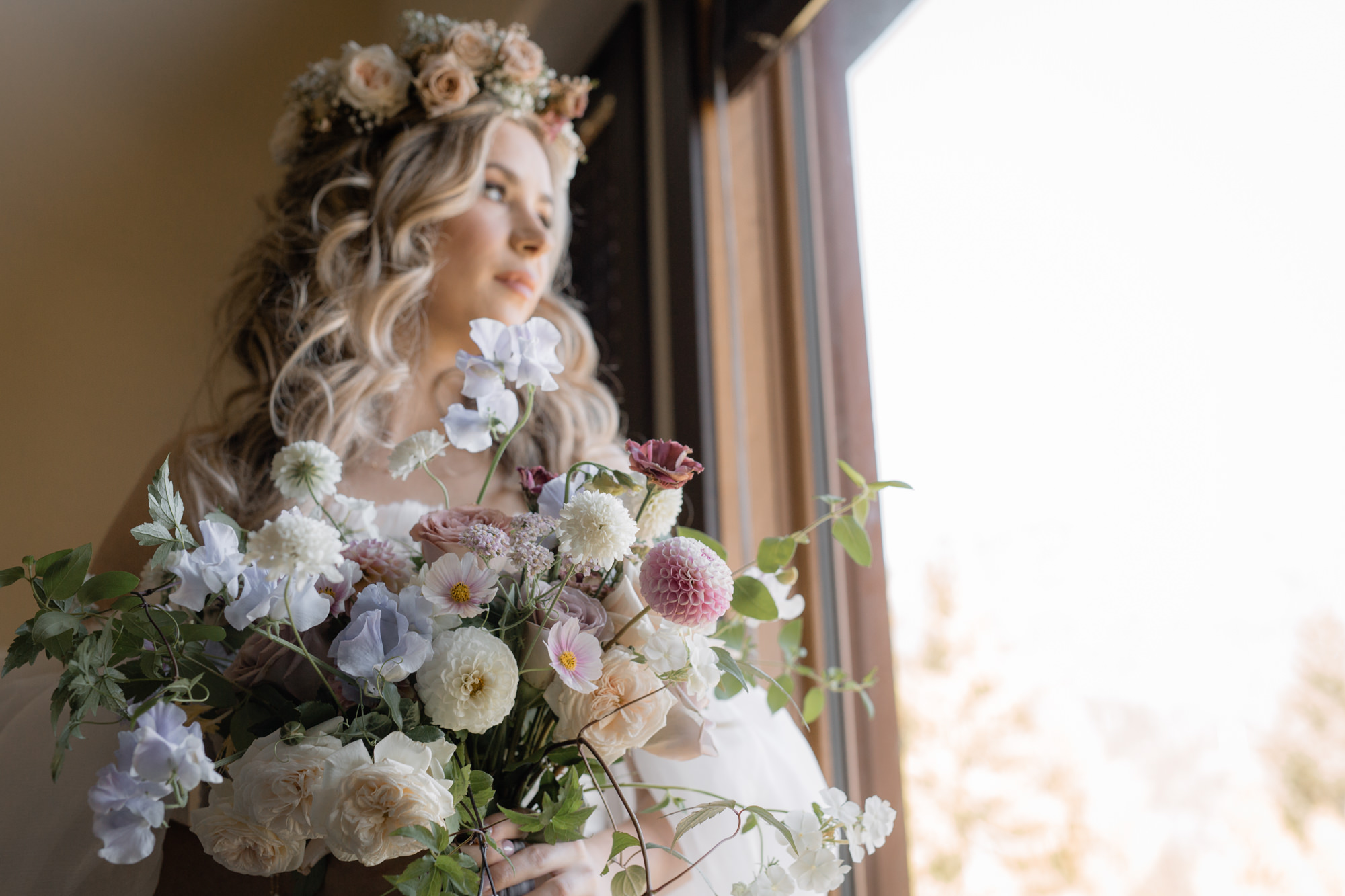 Bride wearing a floral crown and holding her bridal bouquet before her whistler helicopter elopement