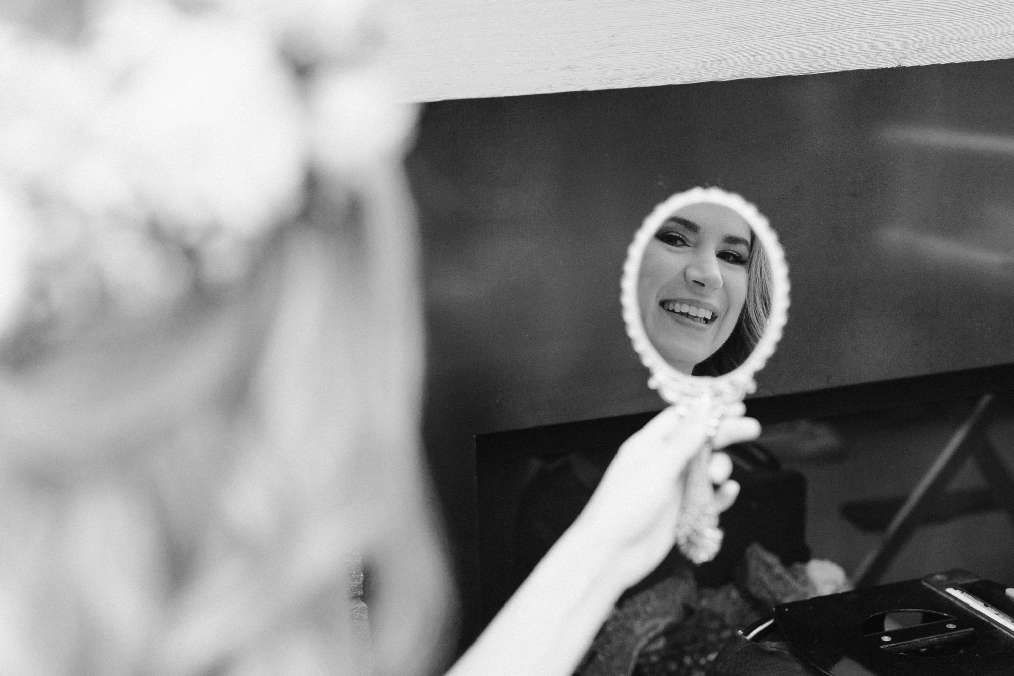 Smiling happy bride looking at herself in the mirror when getting ready for her big day