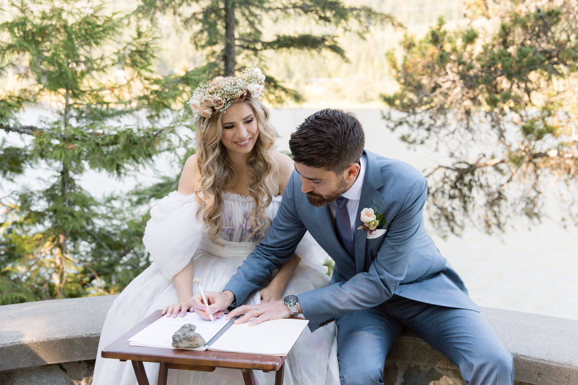 Bride and groom signing official papers after their intimate Stone Circle Wedding Ceremony in Whistler