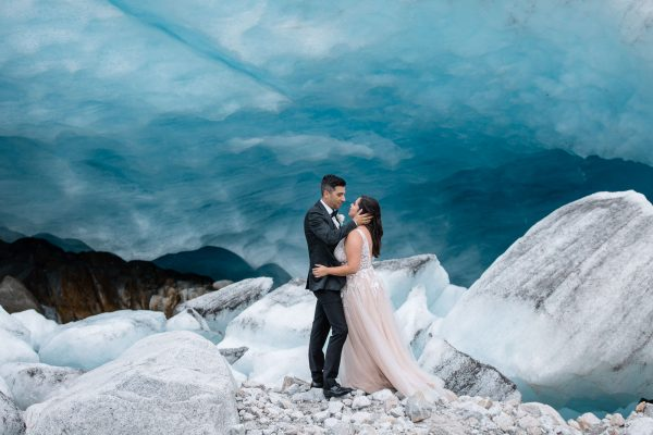 Bride and groom standing in front of giant chunk of blue ice posing for their wedding photos