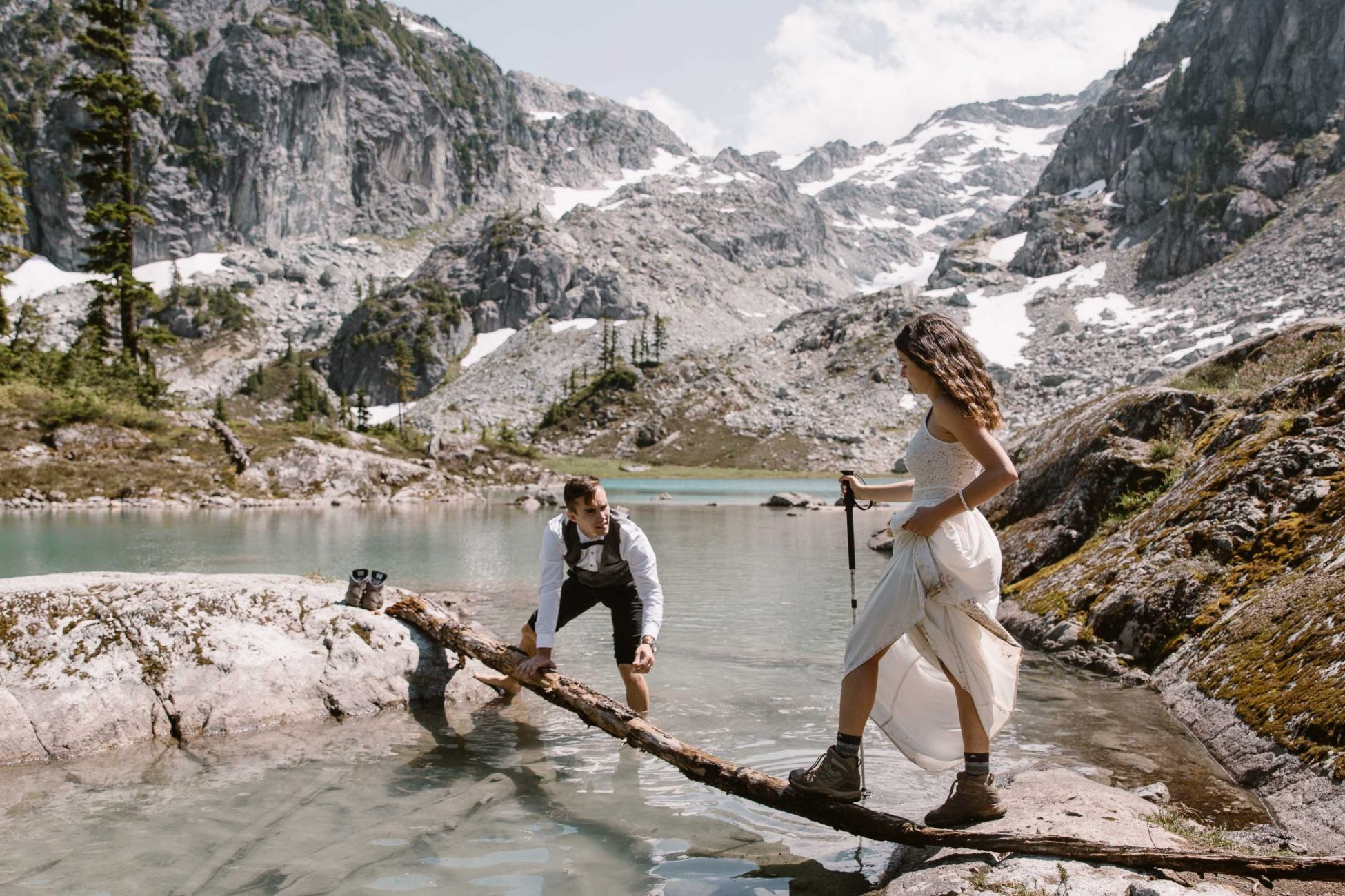 Bride crossing a stream groom is helping her during their adventure elopement