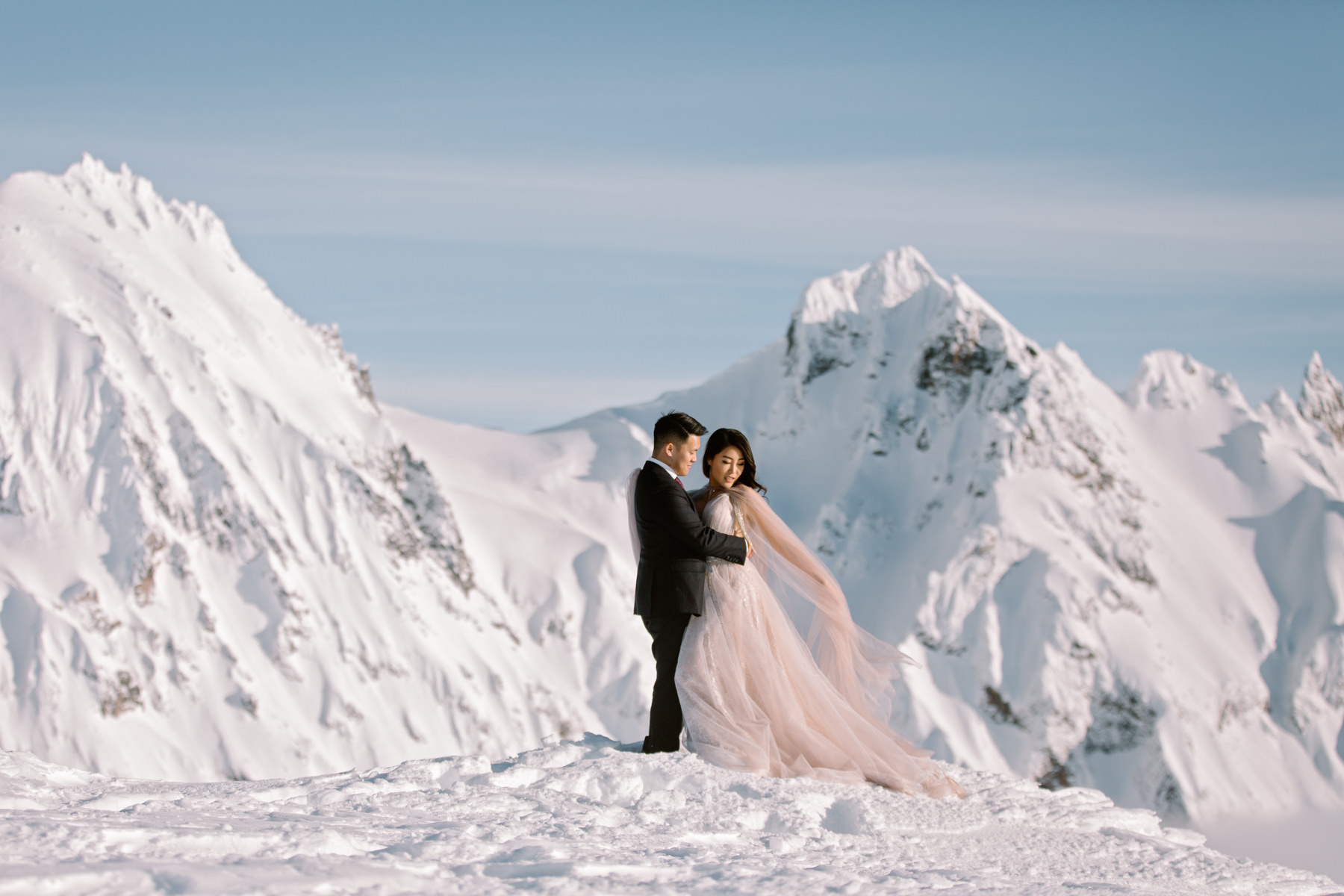 Helicopter elopement packages BC - blush wedding dress in the mountains