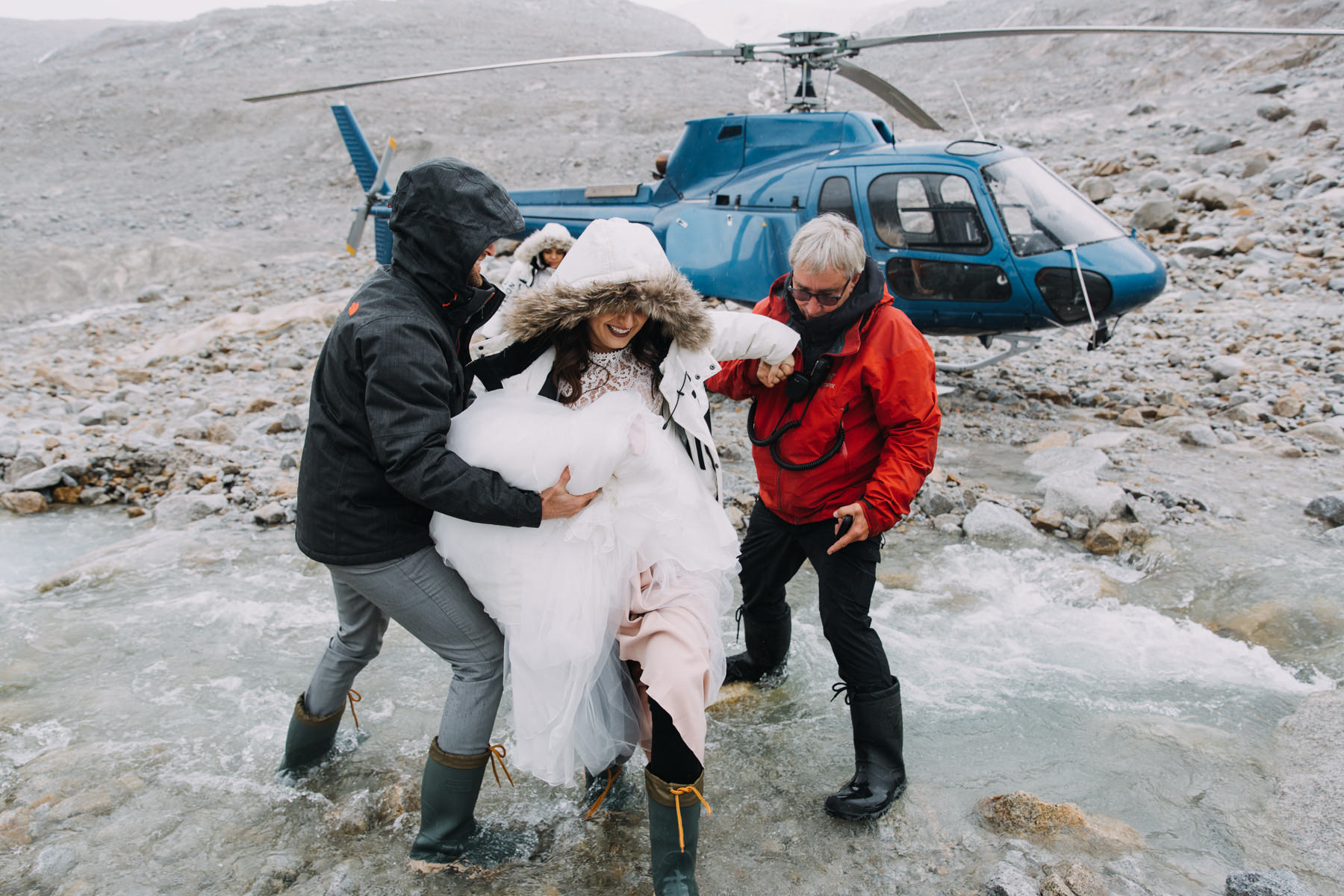 Helicopter elopement packages BC - bride jumping in rain boots