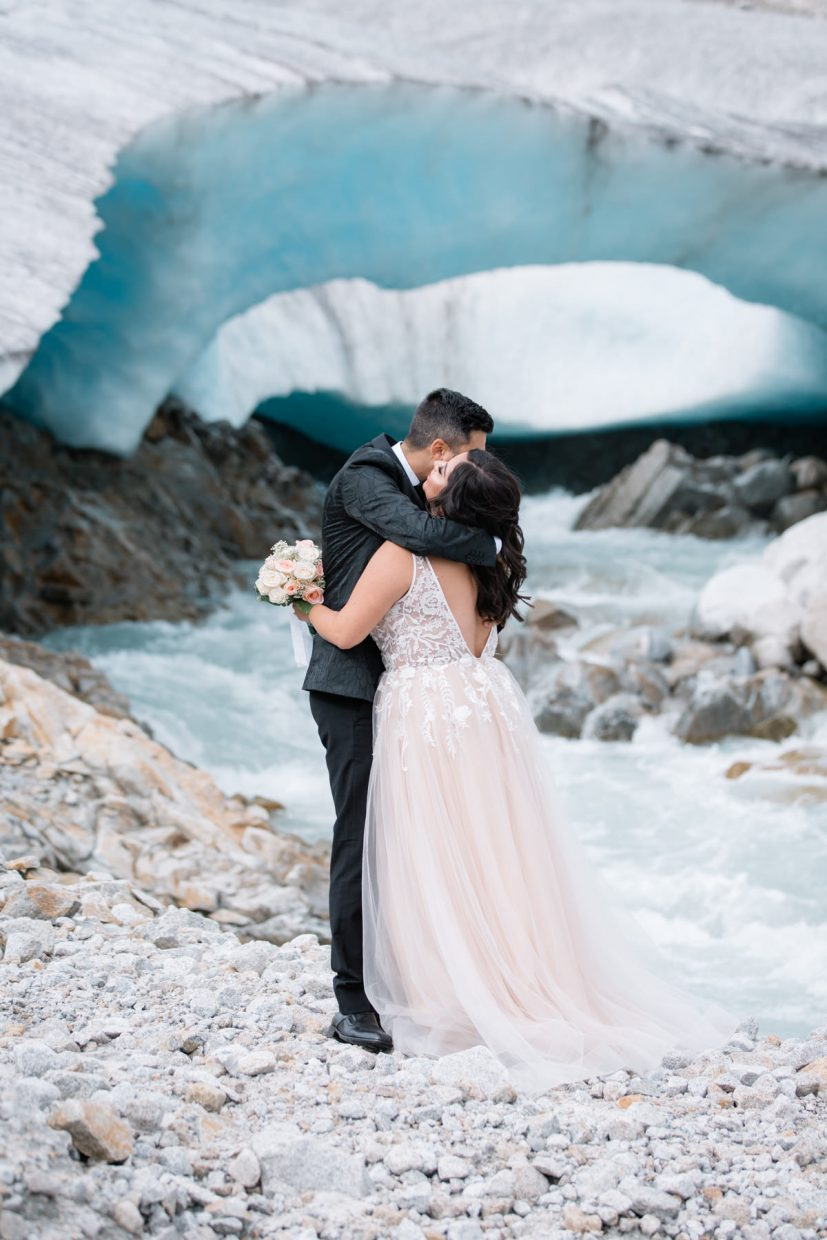 Helicopter elopement packages BC - couple posing in front of the ice cave