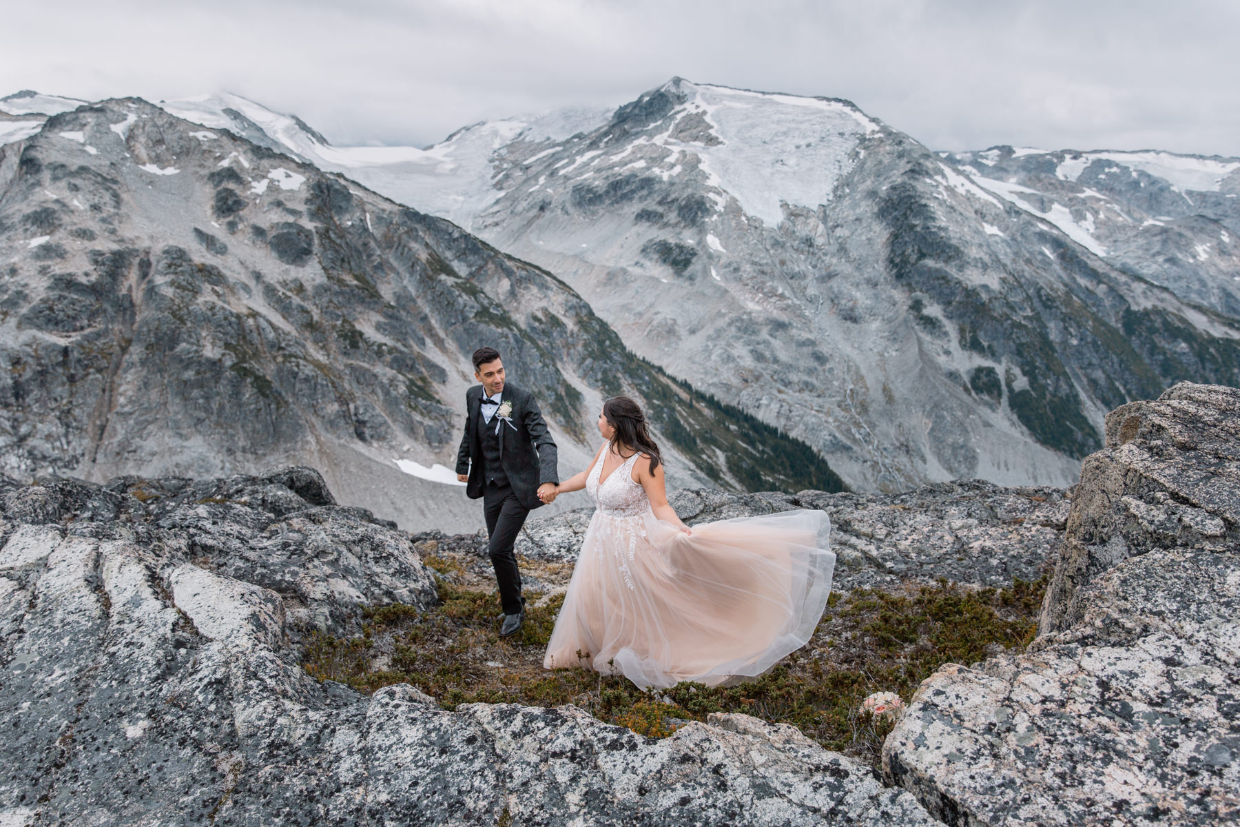 Helicopter elopement packages BC - bride and group in the mountains
