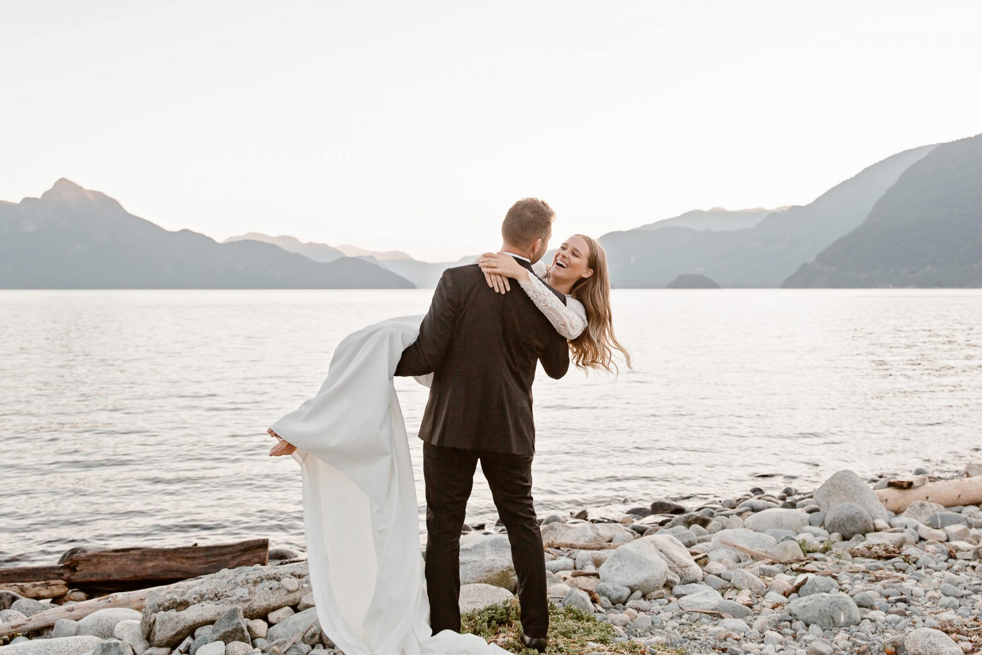 Groom in a black suit is holding a bride in his hands on a west coast beach with a mountain views